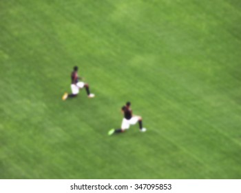 soccer player warm up in the green grass  before the game start in big soccer stadium.-blurred picture.