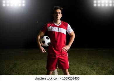 Soccer player wearing red uniform standing on football pitch under lights holding a ball