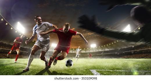 Футболисты в действии на фоне заката стадиона панорамы