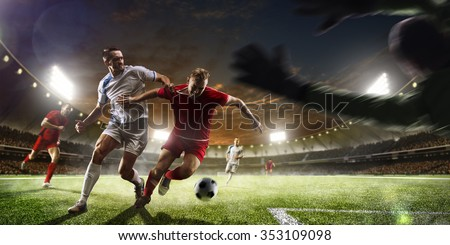 Soccer players in action on the sunset stadium background panorama