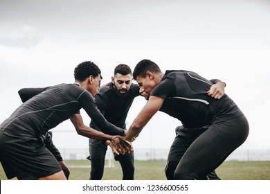 Soccer players discussing game strategy standing in a huddle on the ground. Footballers standing in a huddle holding hands in the centre.