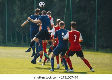 Soccer players heading the ball in competition. Football adult game. Players in two teams compete for the ball. Footballers jumping high on the grass pitch