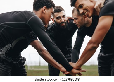 Soccer players joining hands in huddle talking about the game strategy. Low angle view of footballers bending forward in a huddle holding hands.