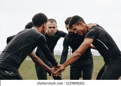 Soccer players joining hands in huddle talking about the game strategy. Footballers bending forward in a huddle holding hands.