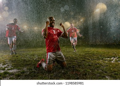 Soccer players on professional soccer night rain stadium. Three dirty players in rain drops emotionally rejoices victory. Black man kneel and scream