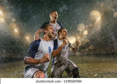 Soccer players on professional soccer night rain stadium. Three dirty players in rain drops emotionally rejoices victory. Men kneel and scream