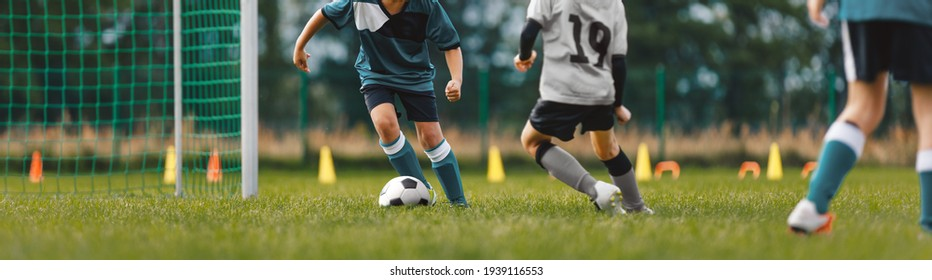 Soccer players on training pitch. Group of young footballers in a duel. Soccer kids running ball in a practice match. School kids playing game on summer training camp