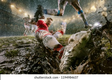 Soccer players performs an action play on a professional night rain stadium. Dirty players in rain drops scores a goal. Grass in the stadium wet from the rain