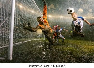 Soccer players performs an action play on a professional night rain stadium. Dirty player in rain drops scores a goal with head. Goalkeeper in flight trying to catch the ball. Grass in the stadium wet