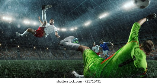 Soccer players performs an action play on a rainy professional stadium. The football goalkeeper catches the ball. All players wears unbranded clothes. The stadium is made in 3D.