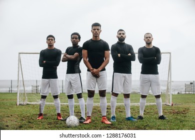 Soccer players standing side by side in front of the goalpost with crossed arms. Group of soccer players standing together on field with a football in front.