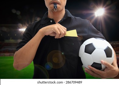 Soccer Referee Showing A Yellow Card In Stadium