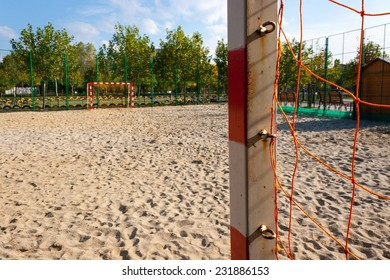 Soccer sand field with red and white gates and orange net.