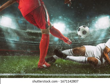 Soccer scene at the stadium with player in a red uniform kicking the ball and opponent in tackle to defend