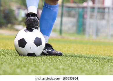 Soccer shoes and football in artificial grass