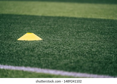 Soccer sport Yellow training equipments marker cone on green outdoor soccer training field ground
