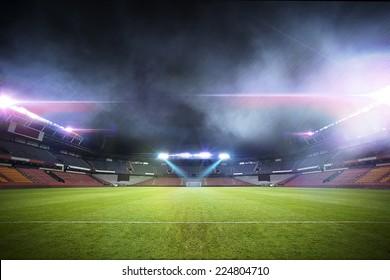 Soccer stadium, arena in night illuminated bright spotlights