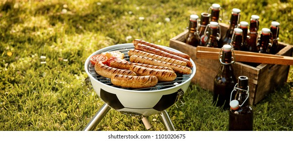 Soccer themed barbecue with pork and beef sausages grilling over a fire in a soccer ball BBQ and crate of beers in a green field in panorama format