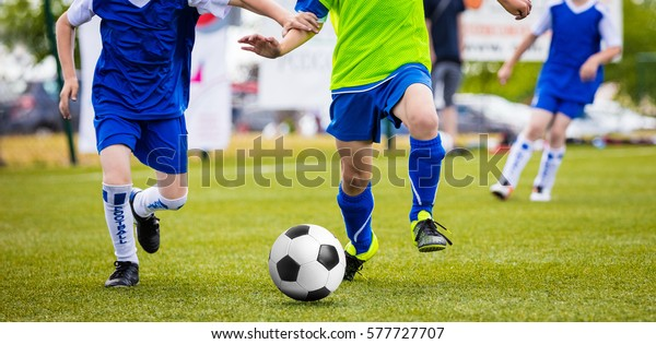 Soccer Training Match For Children Youth Teams. Young Boys Running and Kicking Football Ball on the Pitch