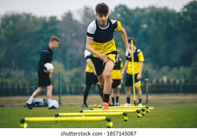 Soccer training on hurdles. Group of young boys in sports football club practicing on jumping hurdles. Youth athletes improving speed skills