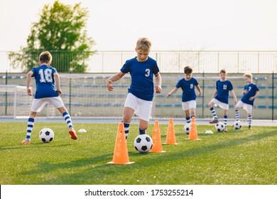 Fußball-Training - Aufwärmen und Slalom Drills. Jungen, die europäischen Fußball auf dem Feld der Grasschule praktizieren