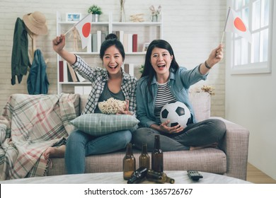 Soccer women fans emotionally watching football game on television in living room. cheerful girls friends with japan flag cheer up on games sitting in couch sofa. happy female eat popcorn with beers