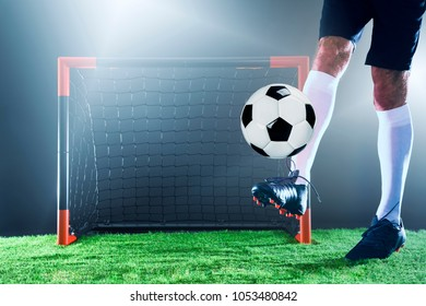 Soccer.Soccer player in front of the goal. Close up on leggs and ball.