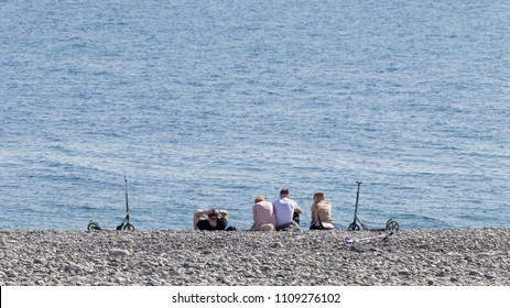 Sochi - April 3, 2017: Two young girls and two young men rest on the pebbled city beach of the Black Sea and two scooters stand nearby April 3, 2017, Sochi, Russia