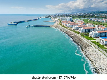 Sochi cityscape and Black sea shore from aerial view. Adler district from above. Resort town in the Caucasus mountains.