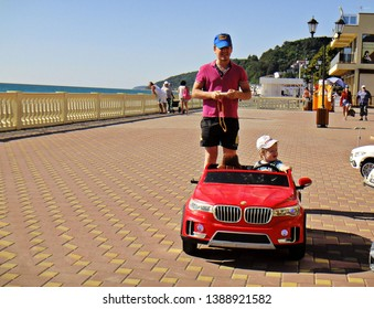 Sochi, Loo, Russia, September 2017 - A little blond boy rides a red typewriter along the Black Sea embankment