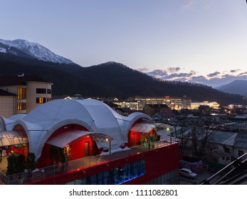Sochi - March 29, 2017: evening view of the city and can be seen: the central shopping center MALL in Rosa Khutor, hotel complexes and snow mountains away March 29, 2017, Sochi, Russia