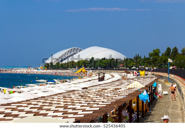 "Sochi, Russia 30 August 2016: on the beach in Sochi View. People sunbathing on the beach. In the background, the Olympic Stadium ""Fischt""."
