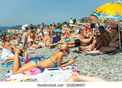 SOCHI, RUSSIA - AUGUST 27, 2017: The central city beach is a bright sunny day in August with tourists resting people sunbathing under the sun and bathed in the black sea