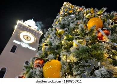Sochi, Russia - December 21, 2017: Christmas tree decorated with illumination lamps and colored balls on a central square with clock tower in the Rosa Khutor ski resort.