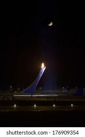 SOCHI, RUSSIA- February 15th: The moon high above the Olympic flame at the Olympic park on February 15th 2014 in Sochi Russia.
