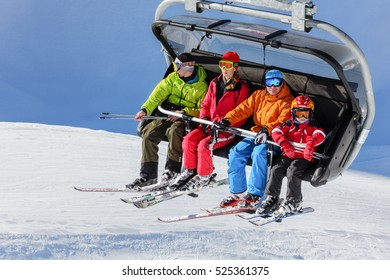 Sochi, Russia - January 20, 2013: Ski slopes in Sochi mountain ski resorts can host ski and snowboard riders for 6 months a year. Family of four people rides on a chair ski lift on a sunny winter day.