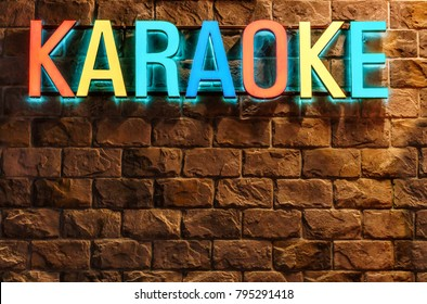 Sochi, Russia - January 4, 2018: Colorful neon illuminated Karaoke sign on stone building wall background at Rosa Khutor resort. Architectural decor of entertainment facilities