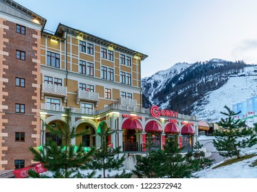 Sochi, Russia - January 6, 2018: Twilight townscape of Gorky Gorod mountain ski resort. Gorky 960 restaurant entrance view with neon exterior sign at winter on snowy mountains background