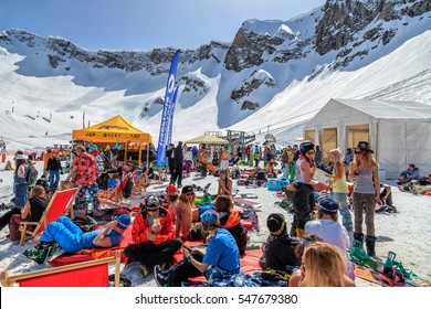Sochi, Russia - March 25, 2014: Quiksilver Camp is a winter mountain sports and entertainment hangout for skiers and snowboarders. Many people chill out relaxing apres ski on the snow on a sunny day