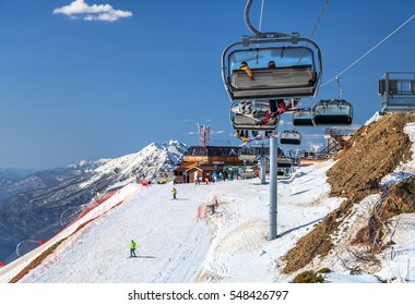 Sochi, Russia - March 25, 2014: Snowy ski slopes of Gorky Gorod ski resort host skiers and snowboarders all winter long. Snowboarders ride on a chair ski lift on blue sky and mountain peak background
