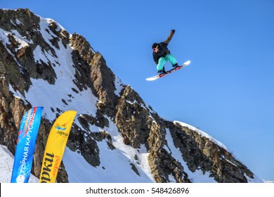 Sochi, Russia - March 25, 2014: Quiksilver Camp is a winter sports and entertainment activity for skiers and snowboarders. Snowboarder flies in the air from a jump on blue sky and mountain background