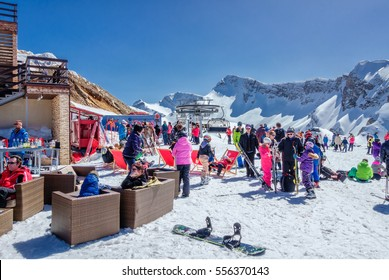 Sochi, Russia - March 25, 2014: Quiksilver Camp is a winter sports and entertainment activity for skiers and snowboarders. Many people chill out apres ski relaxing in the open air under the blue sky.