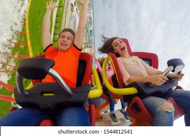 Sochi, Russia - May 8, 2017: Young Caucasian couple of man and woman show expressions while extreme roller coaster ride at Sochi Park