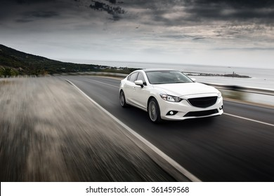 Sochi, Russia - September 7, 2014: Car Mazda fast speed drive on road at sea mountain cloudy sky landscape