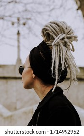 Sochi, Russia - winter 2019. A girl with dreadlocks wearing total black watching aside.