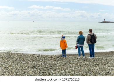 SOCHI,RUSSIA,  18 APRIL 2019 - man, woman and their child stand with backs to the camera on the Black sea shore in cloudy weather