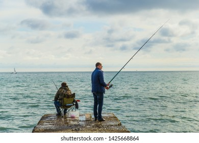 SOCHI,RUSSIA,23 APRIL 2019 -  men fishing on the Black sea,  fishermen on a breakwater with a fishing rod at sunset