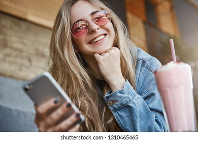 Sociable good-looking girlfriend cannot leave home without smartphone, holding device and chatting while sitting in cozy cafe with boyfriend, drinking cocktail, leaning head on hand
