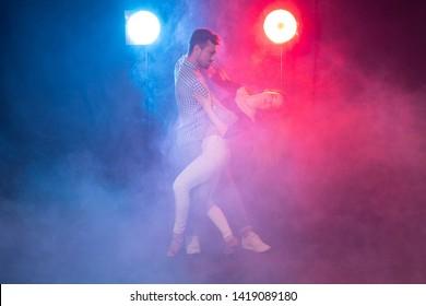 Social dance, bachata, kizomba, zouk and tango concept - Man hugs woman while dancing over lights
