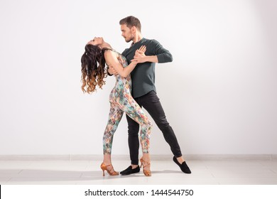 Social dance, bachata, kizomba, zouk, tango concept - Man hugs woman while dancing over white background with copy space